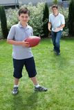 Weinig jongen en vader die Amerikaanse voetbal spelen Stock Afbeeldingen