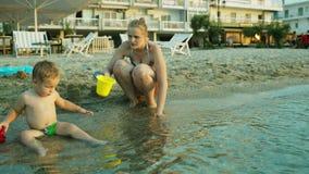Weinig jongen en zijn moeder die op het strand spelen stock footage