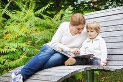 Weinig jongen en zijn moederzitting op bank in park en lezing Stock Foto