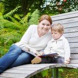 Weinig jongen en zijn moederzitting op bank in park en lezing Stock Afbeelding