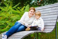 Weinig jongen en zijn moederzitting op bank in park en lezing B royalty-vrije stock afbeelding
