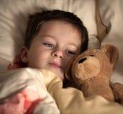 Weinig jongen en zijn teddybeer gaan naar slaap Royalty-vrije Stock Afbeelding