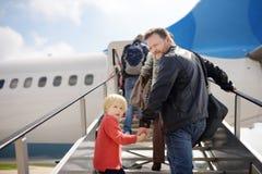 Weinig jongen en zijn vader beklimmen de doorgang in het vliegtuig tegen de achtergrond van mensenpassagier Achter mening stock afbeelding