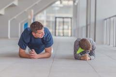 Weinig jongen en zijn vader die duwups oefeningen doen royalty-vrije stock fotografie