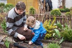 Weinig jongen en zijn vader die zaden in moestuin planten stock afbeelding