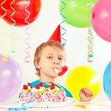 Weinig jongen in feestelijke hoed met verjaardagscake met fluitje en vakantieballons Stock Afbeeldingen