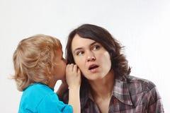 Weinig jongen fluistert aan zijn moeder iets in haar oor Stock Afbeelding