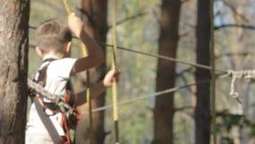 Weinig jongen gaat op een houten brug in een avonturenpark stock video