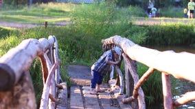 Weinig jongen gaat op houten brug stock video
