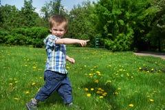 Weinig jongen gaat op weide en wijst op richting Stock Foto