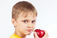 Weinig jongen in geel overhemd met rijpe rode appel Stock Foto