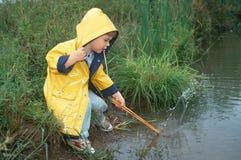 Weinig jongen in gele regenjas door stroom Royalty-vrije Stock Foto's