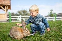 Weinig jongen is gelukkig om een konijn op het landbouwbedrijf te ontmoeten stock afbeeldingen