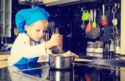 Weinig jongen geniet van kokend in keuken Royalty-vrije Stock Fotografie