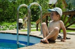 Weinig jongen geniet van zwemmend in de pool Stock Fotografie