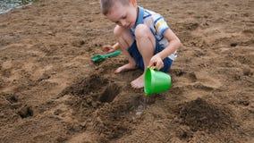 Weinig jongen giet water van een emmer in een gat in het zand Jonge geitjes die op het strand spelen stock footage