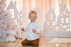 Weinig jongen glimlacht op een Kerstmis achtergronddocument huizen Stock Fotografie