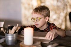 Weinig jongen in grote glazen beeldhouwt van klei met rente stock fotografie