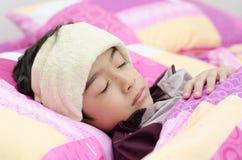 Weinig jongen heeft koorts met handdoek op hoofd stock afbeeldingen