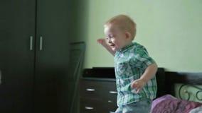 Weinig jongen heeft pret in bed stock videobeelden