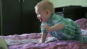 Weinig jongen heeft pret in bed stock footage