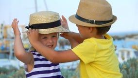 Weinig jongen helpt om de hoed van een klein meisje te kleden stock footage