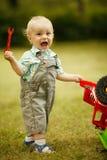 Weinig jongen herstelt stuk speelgoed auto stock afbeelding