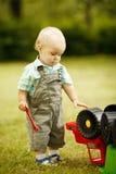 Weinig jongen herstelt stuk speelgoed auto stock fotografie