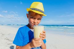 Weinig jongen het drinken cocktail op tropisch strand royalty-vrije stock afbeelding