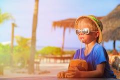 Weinig jongen het drinken kokosnotencocktail op strand stock afbeelding