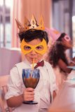 Weinig jongen het drinken sap met het nippen van stro terwijl het zijn bij maskerade royalty-vrije stock afbeeldingen