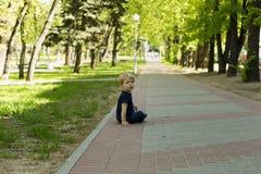 Weinig jongen het jonge geitje in jeans die op de grond daarna in het de zomerpark zitten en camera bekijken Royalty-vrije Stock Afbeelding