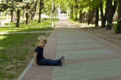 Weinig jongen het jonge geitje in jeans die op de grond daarna in het de zomerpark zitten De ruimte van het exemplaar Stock Afbeelding