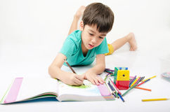 Weinig jongen het kleuren beeld legt op de vloer in concentraat Royalty-vrije Stock Afbeelding