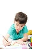 Weinig jongen het kleuren beeld legt op de vloer in concentraat Royalty-vrije Stock Afbeeldingen