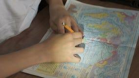 Weinig jongen het leren aardrijkskunde die - kaarten en de bol bekijken stock footage