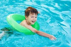 Weinig jongen het leren zwemt met spaarder stock foto