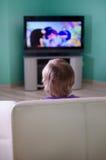 Weinig jongen het letten op beeldverhaal in televisie stock fotografie