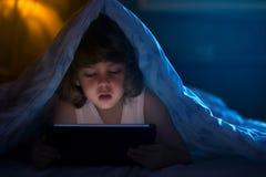 Weinig jongen het letten op beeldverhalen bij nacht royalty-vrije stock afbeeldingen