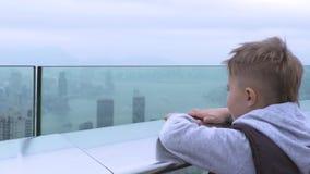 Weinig jongen het letten op stadspanorama van Victoria-piek in Hong Kong-stad, China Toeristenjongen die aan stedelijk landschap  stock video