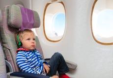 Weinig jongen het letten op televisie tijdens de vlucht stock afbeeldingen