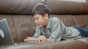 Weinig jongen het letten op video op de laptop computer stock footage