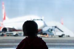 Weinig jongen het letten op vliegtuigen bij de luchthaven Stock Foto's