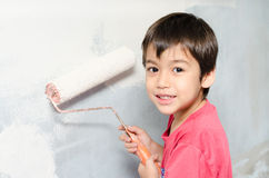 Weinig jongen het schilderen muur witte kleur thuis Royalty-vrije Stock Afbeeldingen