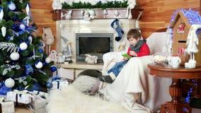 Weinig jongen het schrijven brief aan santa, vakantieatmosfeer, de postcentrum van de Kerstman, ruimte met open haard stock video