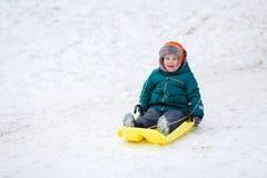 Weinig jongen het sledding Stock Foto