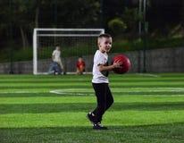Weinig jongen het spelen bal stock foto