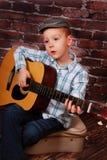 Weinig jongen het spelen gitaar Stock Fotografie
