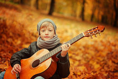 Weinig jongen het spelen gitaar op aardachtergrond, de herfstdag Children& x27; s rente in muziek Stock Afbeelding