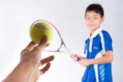 Weinig jongen het spelen tennisracket en tennisbal ter beschikking royalty-vrije stock afbeelding